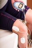 Plan rapproché d'un deportist tenant avec une main la machine électrique et les électrodes d'electrostimulator dans sa jambe Photographie stock
