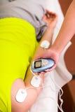 Plan rapproché d'un entraîneur personnel tenant avec une main la machine électrique avec les électrodes d'electrostimulator dans Photo libre de droits