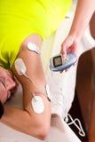 Plan rapproché d'un entraîneur personnel tenant avec une main la machine électrique avec les électrodes d'electrostimulator dans Image libre de droits