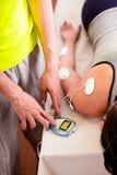Plan rapproché d'un entraîneur personnel touchant avec une main la machine électrique avec les électrodes d'electrostimulator dan Photographie stock