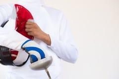 Plan rapproché d'un escrimeur le costume de clôture blanc et en tenant son masque Photos stock