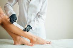 Plan rapproché d'un esthéticien Waxing Woman Leg avec la bande de cire à la station thermale de beauté Photo libre de droits