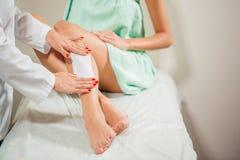 Plan rapproché d'un esthéticien Waxing Woman Leg avec la bande de cire à la station thermale de beauté Photos libres de droits
