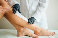 Plan rapproché d'un esthéticien Waxing Woman Leg avec la bande de cire à la station thermale de beauté Photo stock