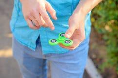 Plan rapproché d'un fileur populaire de vert d'instrument dans la main d'un youn photographie stock libre de droits