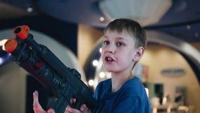 Plan rapproché d'un garçon avec une machine de jouet dans le hall des machines à sous Le garçon joue un jeu vidéo banque de vidéos