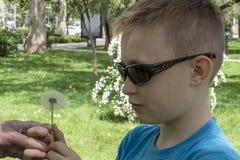 Plan rapproché d'un garçon en lunettes de soleil et pissenlit images libres de droits