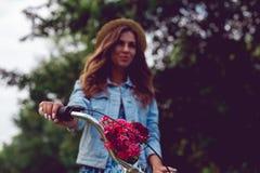 Plan rapproché d'un gouvernail de direction de bicyclette et d'un fond brouillé avec une jeune femme photos stock