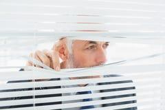 Plan rapproché d'un homme d'affaires jetant un coup d'oeil par des abat-jour dans le bureau Photos libres de droits