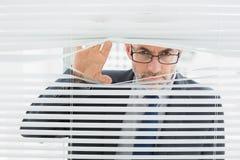 Plan rapproché d'un homme d'affaires jetant un coup d'oeil par des abat-jour dans le bureau Photos stock