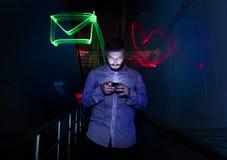Plan rapproché d'un homme employant la nuit de téléphone portable avec le long exposur Photographie stock libre de droits