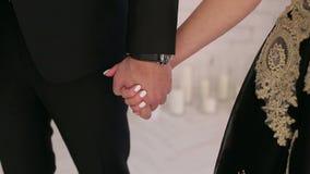 Plan rapproché d'un homme et d'une femme tenant des mains, une fille habillée dans une robe de noir-or banque de vidéos
