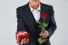 Plan rapproché d'un homme plus âgé sur un fond blanc, dans le studio, dans un costume futé noir avec une rose en sa main et rouge Photographie stock