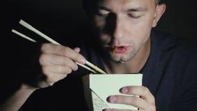 Plan rapproché d'un homme qui mange des nouilles avec des baguettes d'une boîte Nourriture chinoise de consommation européenne clips vidéos