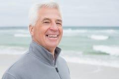 Plan rapproché d'un homme supérieur occasionnel de sourire à la plage Photographie stock