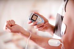 Plan rapproché d'un homme tenant une machine d'électrode dans sa main et avec des électrodes d'electrostimulator dans le bras d'u Photo stock