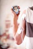 Plan rapproché d'un homme tenant une machine d'électrode dans sa main et avec des électrodes d'electrostimulator dans le bras d'u Images libres de droits