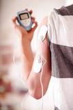Plan rapproché d'un homme tenant une machine d'électrode dans sa main et avec des électrodes d'electrostimulator dans le bras d'u Photo libre de droits