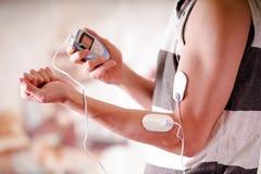 Plan rapproché d'un homme tenant une machine d'électrode dans sa main et avec des électrodes d'electrostimulator dans le bras d'u Image stock
