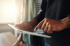 Plan rapproché d'un homme touchant sur le comprimé numérique photographie stock