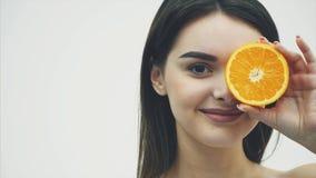 Plan rapproché d'un jeune beau modèle de fille d'une tranche d'orange sur un fond blanc Avec le maquillage et le beau noir banque de vidéos