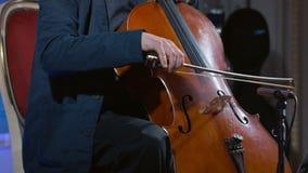 Plan rapproché d'un joueur de violoncelle cintrant son instrument banque de vidéos