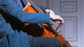 Plan rapproché d'un joueur de violoncelle cintrant son instrument clips vidéos