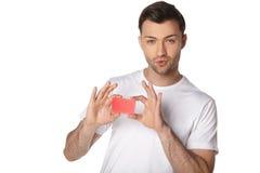 Plan rapproché d'un mâle tenant la carte de crédit en blanc Image stock