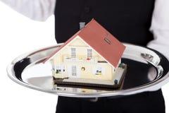Plan rapproché d'un maître d'hôtel avec le modèle d'une maison Image stock