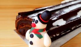 Plan rapproché d'un massepain mignon de bonhomme de neige avec du chocolat brouillé Yule Log Cake à l'arrière-plan d'isolement su image stock