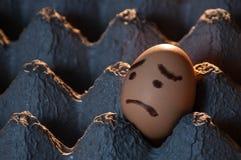 Plan rapproché d'un oeuf au visage triste dans un plateau d'oeufs Photo libre de droits
