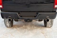 Plan rapproché d'un pare-chocs de luxe noir de voiture de SUV avec les pots d'échappement bilatéraux de turbo dehors pendant l'hi photo stock
