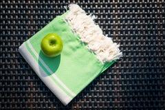 Plan rapproché d'un peshtemal turc/de serviette blanche et verte et de pomme verte sur un canapé de rotin Image stock
