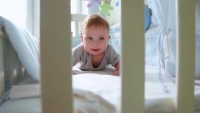 Plan rapproché d'un petit enfant en bas âge dans une huche riant la vue de côté par le treillis d'une huche Enfance heureux, joie banque de vidéos