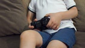 Plan rapproché d'un petit garçon tenant une manette et jouant des jeux vidéo à la maison clips vidéos