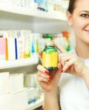 Plan rapproché d'un pharmacien féminin brouillé donnant des comprimés en BO Image libre de droits