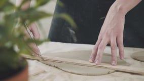 Plan rapproché d'un potier principal, argile coupant l'outil spécial Burin pour l'argile banque de vidéos