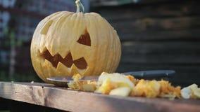 Plan rapproché d'un potiron et d'une lanterne Jack se trouvant sur la table, à côté des légumes de coupe La main femelle met un c banque de vidéos