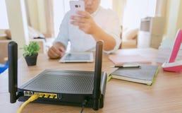 Plan rapproché d'un routeur sans fil et d'un homme à l'aide du smartphone sur l'ofiice de salon à la maison Images stock