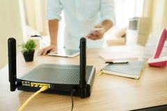 Plan rapproché d'un routeur sans fil et d'un homme à l'aide du smartphone sur l'ofiice de salon à la maison Image stock