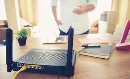 Plan rapproché d'un routeur sans fil et d'un homme à l'aide du smartphone sur l'ofiice de salon à la maison Images libres de droits