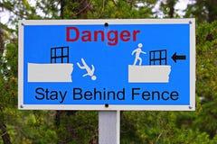 Plan rapproché d'un séjour de danger derrière le signe de barrière Photo libre de droits