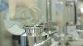Plan rapproché d'un scientifique versant un liquide d'un tube à essai dans un équipement Liquide de versement de scientifique des clips vidéos
