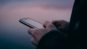 Plan rapproché d'un smartphone au coucher du soleil Technologie moderne et l'Internet Orientation peu profonde Images stock