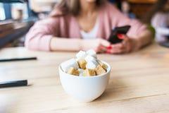 Plan rapproché d'un sucrier avec des cubes en sucre À l'arrière-plan, la fille à la table à l'intérieur du café emploie images libres de droits