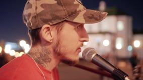 Plan rapproch? d'un type chantant avec une guitare dans le microphone Discours la nuit dans la place de ville Bel ?clairage clips vidéos