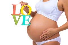 Plan rapproché d'un ventre enceinte avec un amour de label de signe d'isolement sur un fond blanc Photographie stock
