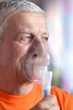 Vieil homme faisant l'inhalation Image stock