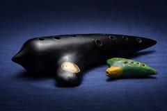 Plan rapproché d'un vieil okarina vert moyen et petit noir images libres de droits