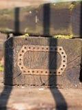 Plan rapproché d'un vieux bloc de bois avec un morceau de fer avec des trous attachés sur la surface images stock